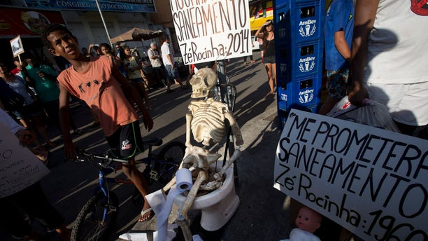 """A plastic skeleton sits on a toilet with a banner attached that reads in Portuguese; """"I'm still waiting for sanitation, signed Ze Rocinha: 2014,"""" alongside a doll that sits on a potty with a banner that reads in Portuguese: """"They promised me sanitation, signed Ze Rocinha: 1960,"""" during a demonstration organized by the pro-sanitation group Meu Rio at the Rocinha slum, in Rio de Janeiro, Brazil, Saturday, Feb. 22, 2014. Ze Rocinha is a character invented by Rocinha slum residents. Meu Rio aims to draw attention to the Olympic city's massive sewage problem. Only 30 percent of Rio's sewage is treated, and the rest flows raw into its waterways. (AP Photo/Silvia Izquierdo)"""