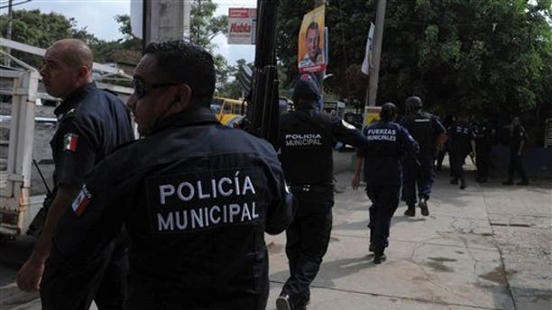 Police react as gunmen on vehicles shoot at them outside a police station in Acapulco, Mexico, Saturday, Jan. 8, 2011. This weekend got off to a bloody start with 27 people killed there from Friday evening to early Saturday, according to local police authorities. (AP Photo)