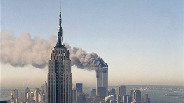 Sept. 11, 2001: In this file photo, the twin towers of the World Trade Center burn behind the Empire State Building in New York.