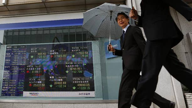 People walk past an electronic stock board showing the global financial index at a securities firm in Tokyo, Thursday, March 24, 2016. Asian stock markets fell for a second day Thursday after declines in prices of oil and other commodities pulled Wall Street lower. (AP Photo/Shuji Kajiyama)