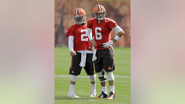 Cleveland Browns quarterback Brian Hoyer (6) and Johnny Manziel (2) wait for a passing drill during practice at the NFL football team's facility in Berea, Ohio, Wednesday, Sept. 17, 2014. Hoyer, who drove 85 yards to set up the game-winning field goal Sunday against the New Orleans Saints, showed that the Browns are his team and Manziel has to watch and learn, for now. (AP Photo/Mark Duncan)