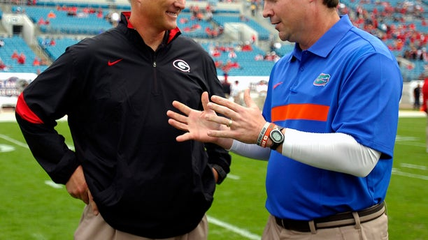 FILE - In this Oct. 29, 2011, file photo, Florida coach Will Muschamp, right, and Georgia coach Mark Richt talk before an NCAA college football game in Jacksonville, Fla. Georgia and Florida, teams that began the year with championship aspirations, have been ravaged by injuries and enter their annual Cocktail Party game at Jacksonville staring at the final gasp to make something of their disappointing seasons. (AP Photo/Stephen Morton, File)