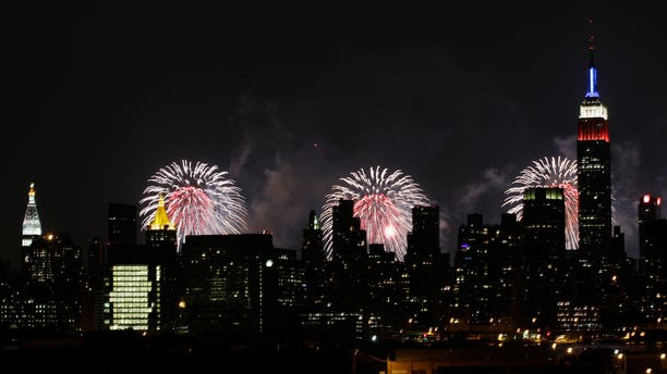 The Empire State Building, illuminated with red, white and blue lights, is seen from the Queens borough of New York, backlit by fireworks over the Hudson River, during the Macy's Fourth of July fireworks show Wednesday, July 4, 2012, in New York.  (AP Photo/Frank Franklin II)