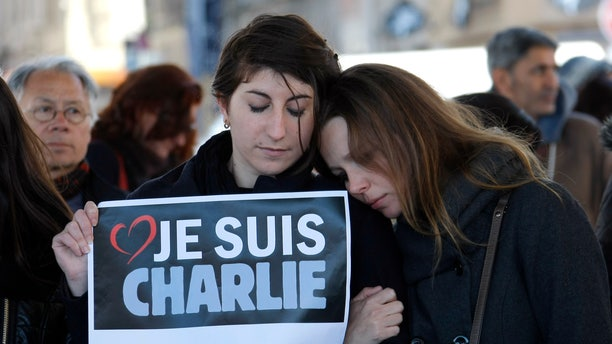 "People pay tribute to the victims of the satirical newspaper ""Charlie Hebdo"", in Marseille, southern France, Thursday, Jan. 8, 2015, a day after masked gunmen stormed the offices of a satirical newspaper and killed 12 people. French police hunted Thursday for two heavily armed men — one with a terrorism conviction and a history in jihadi networks — in the methodical killing of 12 people at a satirical newspaper that caricatured the Prophet Muhammad. Placard reads ""I am Charlie"" . (AP Photo/Claude Paris)"
