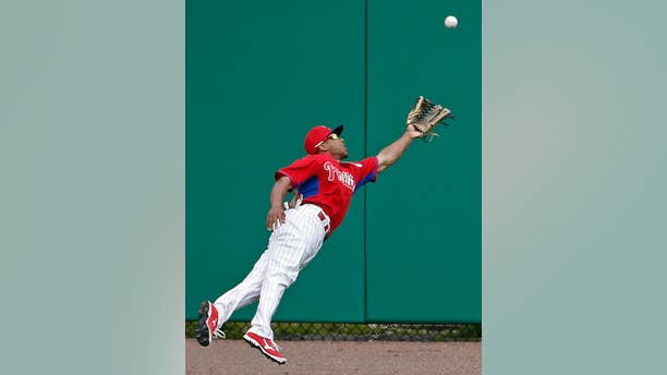 Philadelphia Phillies center fielder Ben Revere (2) dives for Atlanta Braves Gerald Laird's fourth-inning double in a spring exhibition baseball game in Clearwater, Fla., Monday, March 10, 2014.  (AP Photo/Kathy Willens)