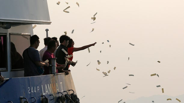 Oct. 2, 2012: Relatives of the victims throw paper money as they pay tribute to the ill-fated people aboard a boat that sank Monday night near Lamma Island, off the southwestern coast of Hong Kong Island.