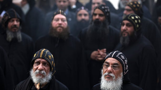Clergymen gather to wait for the arrival of Egypt's Coptic Christian Pope Tawadros II, at the historic al-Muharraq Monastery, a centuries-old site some 180 miles (300 kilometers) south of Cairo in the province of Assiut, Egypt, Tuesday, Feb. 5, 2013. Egypt's Coptic Christian pope sharply criticized the country's Islamist leadership in an interview with The Associated Press on Tuesday, saying the new constitution is discriminatory and Christians should not be treated as a minority. (AP Photo/Khalil Hamra)