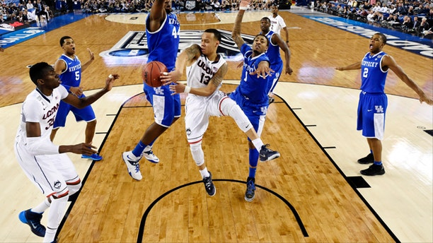 April 7, 2014: Connecticut guard Shabazz Napier (13) passes around Kentucky center Dakari Johnson (44) to center Amida Brimah (35) as guard James Young (1) helps during the first half of the NCAA Final Four tournament college basketball championship game in Arlington, Texas. (AP Photo/Chris Steppig, pool)