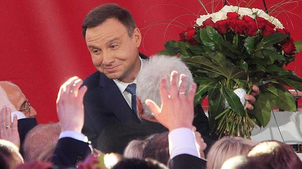 May 24, 2015: Opposition candidate Andrzej Duda celebrates with supporters as the first exit polls in the presidential runoff voting are announced in Warsaw. (AP Photo/Czarek Sokolowski)