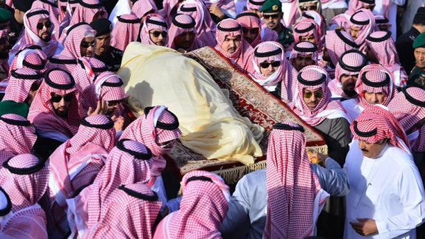 In this Friday, Jan. 23, 2015 photo, provided by the Saudi Press Agency, members of the Saudi royal family carry the body of King Abdullah, who died early Friday during his funeral in Riyadh, Saudi Arabia. In line with the strict interpretation of Islamic tradition observed in the kingdom, Abdullah was buried in an unadorned, beige cloth without a coffin in an unmarked grave. World leaders and top dignitaries began arriving in Saudi Arabia on Saturday, Jan. 24, 2015 to give their condolences following the death of King Abdullah at age 90  after nearly two decades at the helm. (AP Photo/SPA)