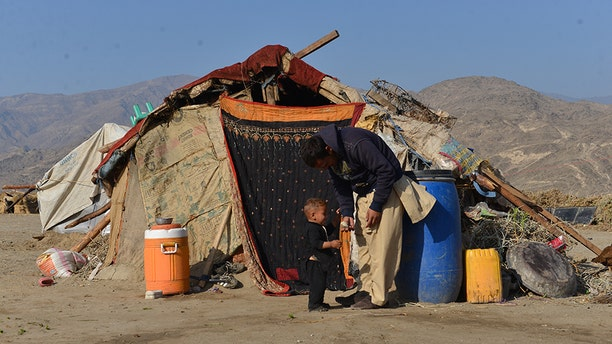 A man who recently came back to Afghanistan from Pakistan plays with his son outside their tent in a camp for returnees.