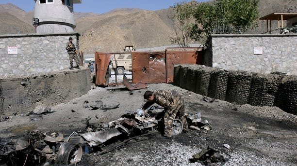 An Afghan security officer, center, collects evidence from the site of an attack by militants at the gate of an American base in Panjshir north of Kabul, Afghanistan, Saturday, Oct. 15, 2011.
