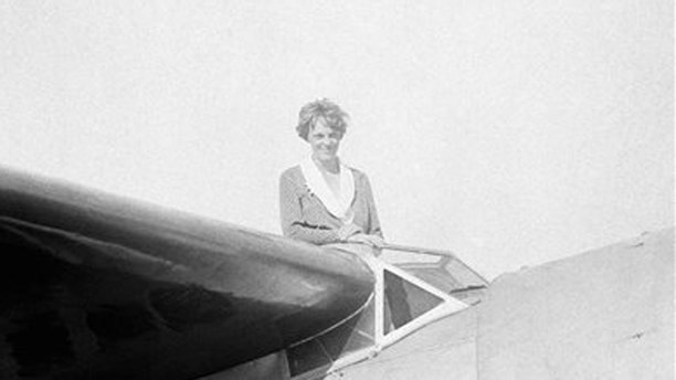 FILE - In this undated photo, Amelia Earhart, the first woman to cross the Atlantic Ocean by plane sits on top of a plane.