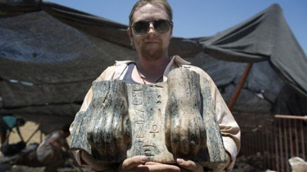 July 9, 2013: An Australian excavation volunteer displays part of an ancient Egyptian king's unique sphinx with a hieroglyphic inscription dating circa 3rd century BCE, found during excavation at the northern Israeli site of ancient Tel Hazor.