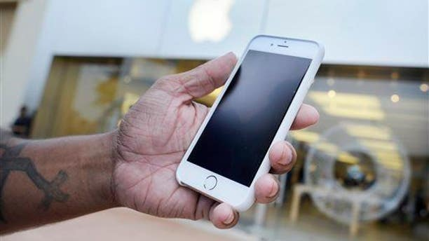 A customer holds his new iPhone 6 at an Apple Store in Augusta, Ga.