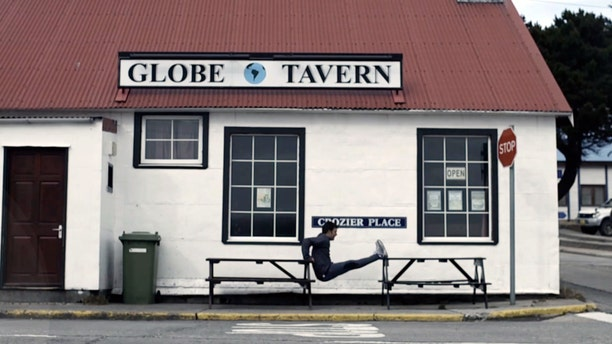 In this frame grab from a TV advertisement released by Argentine Presidential Office, an Argentine Olympic field hockey player Fernando Zylberberg exercises in front of the Globe Tavern in Stanley, Falkland Islands.