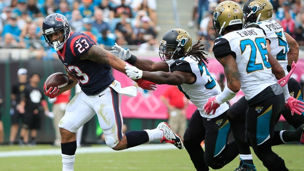 Arian Foster of the Houston Texans rushes against  Davon House of the Jacksonville Jaguars on Oct. 18, 2015.