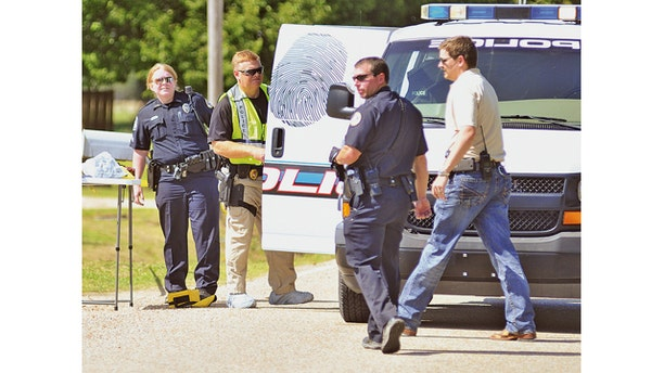 May 3, 2014: Jonesboro, Ark. police officers and crime scene analysts investigate a crime scene.  Jonesboro Sgt. Doug Formon said a man and a 13-year-old girl were killed Saturday afternoon inside a residence in east Jonesboro, Arkansas. Four other people, including two boys, were injured and were taken to hospitals in Memphis, Tennessee. He said the children, ages 8 and 10, were transported in critical condition. (AP Photo/The Jonesboro Sun, Rob Holt)