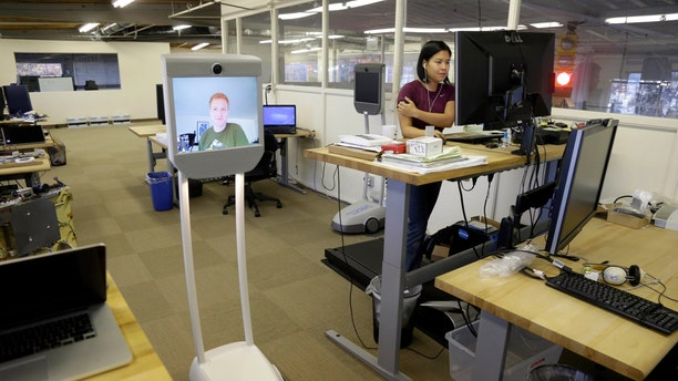Dec. 12, 2012: Senior software engineer, Josh Faust, seen on screen, navigates his company's office using a Beam remote presence system, as fellow engineer Stephanie Lee, at right, works on a project at Suitable Technologies in Palo Alto, Calif.