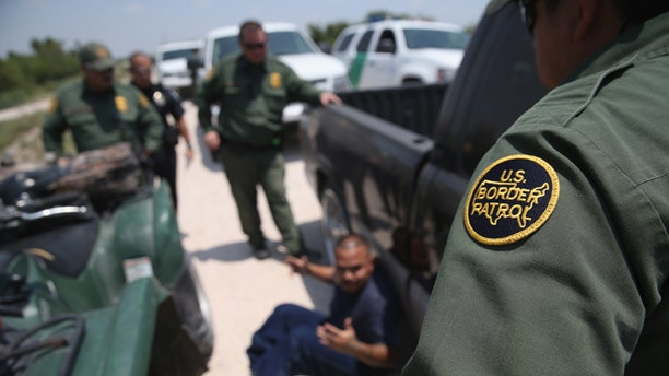 MISSION, TX - JULY 24:  U.S. Border Patrol agents detain a suspected smuggler after he allegedly transported undocumented immigrants who crossed the Rio Grande from Mexico into the United States on July 24, 2014 in Mission, Texas. Tens of thousands of undocumented immigrants, many of them unaccompanied minors, have crossed illegally into the United States this year and presented themselves to federal agents, causing a humanitarian crisis on the U.S.-Mexico border.  (Photo by John Moore/Getty Images)