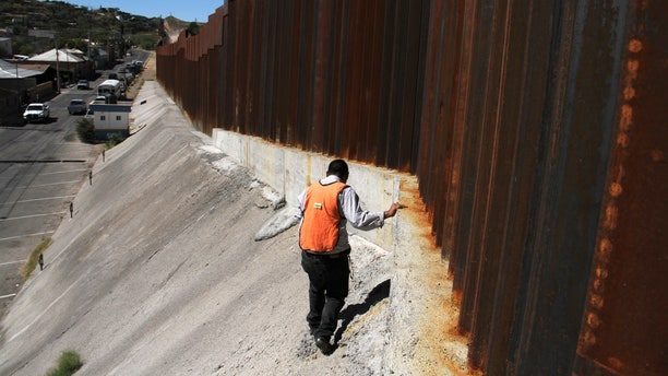 FILE: Oct. 12, 2012: An investigator inspects a crime scene where a suspected drug smuggler was shot by  a U.S. Border Patrol agent on the Mexico-Arizona border.