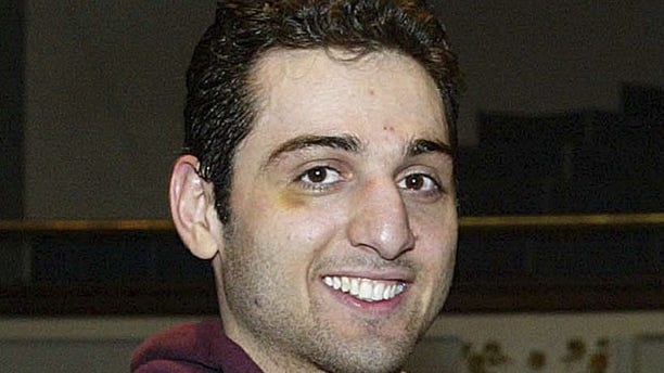 FILE - In this Feb. 17, 2010, file photo, Tamerlan Tsarnaev smiles after accepting the trophy for winning the 2010 New England Golden Gloves Championship in Lowell, Mass. Prosecutors in the case against Boston Marathon bombing suspect Dzhokhar Tsarnaev, Tamerlan's brother, say a man shot to death during questioning by an agent in Florida told investigators that Tamerlan had been involved in a triple homicide (AP Photo/The Lowell Sun, Julia Malakie File)