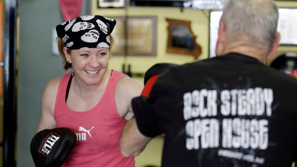 Kristy Rose Follmar spars with a class participant during a workout at Rock Steady Boxing in Indianapolis. Rock Steady boxing is a unique nonprofit gym that, since 2006, has offered a uniquely effective form of physical exercise to people who are living with Parkinson's.