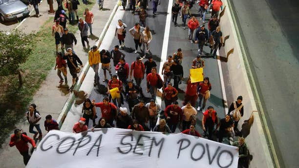 "Members of the Homeless Workers Movement holding a banner that reads in Portuguese ""World Cup without the People, then I am in the street again"", march during a protest demanding better public services and against the money spent on the World Cup preparations in Sao Paulo, Brazil, Wednesday, June 4, 2014. (AP Photo/Nelson Antoine)"