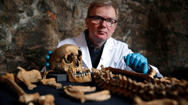 March 26, 2014: Don Walker, a human osteologist with the Museum of London, poses for photographers, with one of the skeletons found by construction workers under central London's Charterhouse Square. Twenty-five skeletons were uncovered last year during work on Crossrail, a new rail line that's boring 13 miles of tunnels under the heart of the city. Archaeologists immediately suspected the bones came from a cemetery for victims of the bubonic plague that ravaged Europe in the 14th century. The Black Death, as the plague was called, is thought to have killed at least 75 million people, including more than half of Britain's population. (AP Photo/Lefteris Pitarakis)