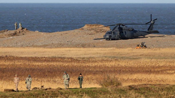 Jan. 8, 2014: The wreckage of a US Military Air Force Pave Hawk helicopter, partially obscured in front of helicopter right, lies on the ground in Salthouse, England, after the helicopter crashed late Tuesday killing all four crew members aboard.