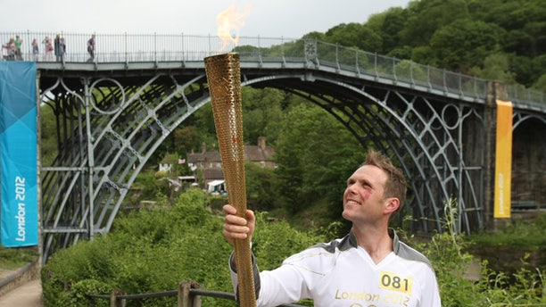 Lyndon Flavell holds the Olympic Flame next to the Iron Bridge at Ironbridge Gorge between Much Wenlock and Telford in central England.