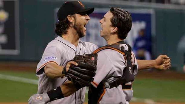 October 29 ,2104: San Francisco Giants pitcher Madison Bumgarner, left, and Buster Posey celebrate after defeating the Kansas City Royals in Game 7 of baseball's World Series in Kansas City, Mo. (AP Photo/Matt Slocum)
