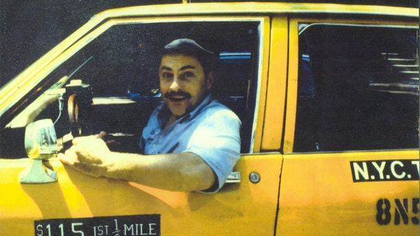 """Jerry Torre, also known as the """"Marble Faun,"""" driving a taxi in New York City."""