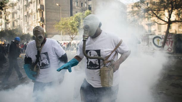 November 23, 2011: Protesters attempt to get rid of a tear gas canister during clashes with Egyptian riot police, not pictured, near Tahrir square in Cairo, Egypt.