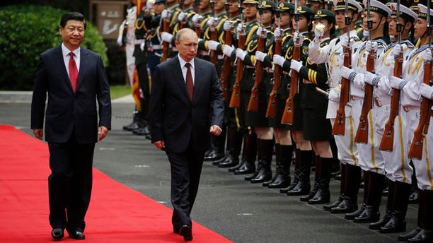 May 20, 2014: Russia's President Vladimir Putin, center, and China's President Xi Jinping, left, review an honor guard during a welcoming ceremony at the Xijiao State Guesthouse ahead of the fourth Conference on Interaction and Confidence Building Measures in Asia (CICA) summit in Shanghai. (AP Photo/Carlos Barria, Pool)