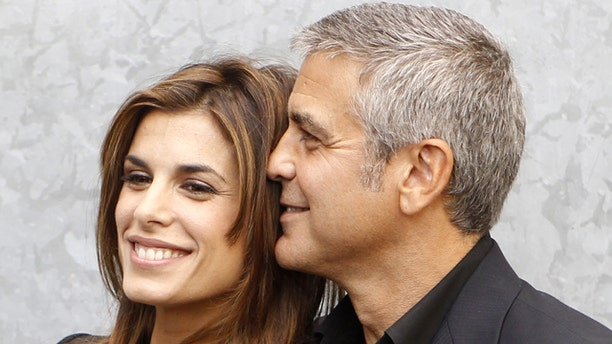 George Clooney poses with his girlfriend Elisabetta Canalis before the Giorgio Armani Spring/Summer 2011 women's collection during Milan Fashion Week September 27, 2010.