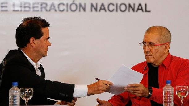 Frank Pearl, head of Colombia's peace negotiation team, left, hands documents to Antonio Garcia, chief negotiator of the National Liberation Army, or ELN, during a signing agreement to start peace talks, in Caracas, Venezuela, Wednesday, March 30, 2016. The formal peace talks with the ELN, the country's second-largest rebel group, heightens expectations for a definitive end to a half-century of political violence in the Andean nation. (AP Photo/Ariana Cubillos)