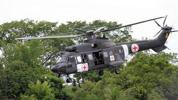 April 2, 2012: A Brazilian air force helicopter emblazoned with the Red Cross logo takes off from an airfield to pick up members of the last group of soldiers and police held by Colombia's main rebel group, in Villavicencio, Colombia.
