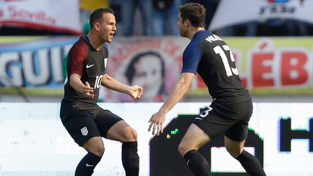 United States' Luis Gil, left, celebrates with teammate Matt Polster after scoring his side's first goal against Colombia  during a U-23 first leg soccer match qualifier for the 2016 Rio Olympics at the Roberto Melendez Stadium in Barranquilla, Colombia, Friday, March 25, 2016. (AP Photo/Fernando Vergara)