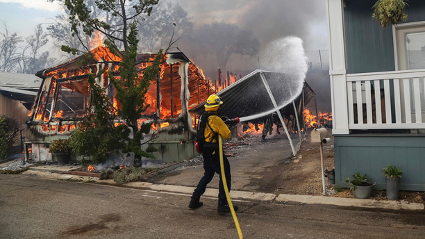 Firefighters battle flames at the Alpine Oaks Estates mobile home park during a wildfire Friday in Alpine, California.