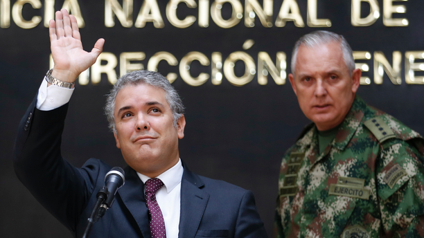 """Colombia's President Ivan Duque, left, waves next to the Commander of the Armed Forces Gen. Alberto Mejia, during a press conference at police headquarters in Bogota, Colombia, Wednesday, Sept. 19, 2018. Duque said that Colombian armed forces continue with operations against a dissident rebel of the now disbanded Revolutionary Armed Forces of Colombia known as """"Guacho"""". (AP Photo/Fernando Vergara)"""