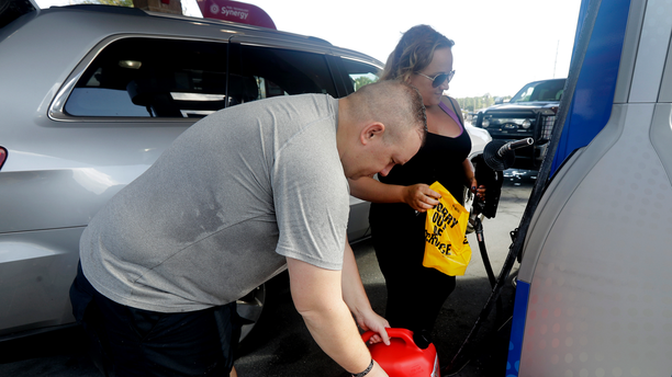"""Sarah Dankanich, right, removes an """"out of service"""" wrapper from a gas pump as her husband, Bryan Dankanich, left, prepares to pump gas in cans in advance of Hurricane Florence in Wilmington, N.C., Wednesday, Sept. 12, 2018. Florence exploded into a potentially catastrophic hurricane Monday as it closed in on North and South Carolina, carrying winds up to 140 mph (220 kph) and water that could wreak havoc over a wide stretch of the eastern United States later this week. (AP Photo/Chuck Burton)"""