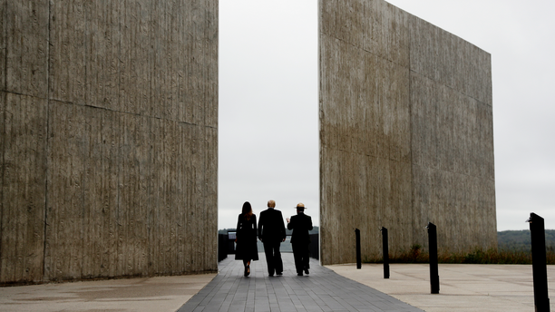 """In this Sept. 11, 2018, photo, President Donald Trump and first lady Melania Trump, escorted by Stephen Clark, Superintendent of the National Parks of Western Pennsylvania, walk along the September 11th Flight 93 memorial in Shanksville, Pa. Trump says the Sept. 11 memorial in Shanksville renewed his resolve to push for his stalled southern border wall. Trump tells Hill.TV in an interview published Sept. 19 that he marveled at the Flight 93 National Memorial during a visit. Trump says, """"They built this gorgeous wall where the plane went down."""" He says, """"What they did is incredible,"""" adding: """"They have a series of walls, I'm saying, it's like perfect. So, so, we are pushing very hard."""" (AP Photo/Evan Vucci)"""