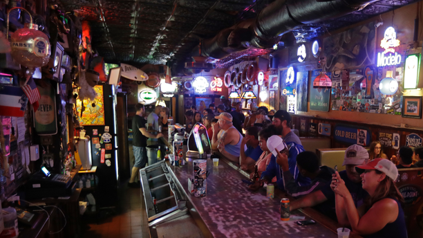 Locals have a drink as they relax at the Barbary Coast bar in downtown Wilmington, N.C., as  Florence threatens the coast Thursday, Sept. 13, 2018. (AP Photo/Chuck Burton)
