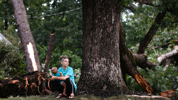 Sierra Price and son, Ryland Ross, 10 months, wait outside their home at Julian and Glendale Streets as work begins on cleanup in the area near Richmond,Virginia on Tuesday, Sept. 18, 2018, the day after Florence-spawned tornadoes caused damage and claimed one life in the area.( Joe Mahoney/Richmond Times-Dispatch via AP)