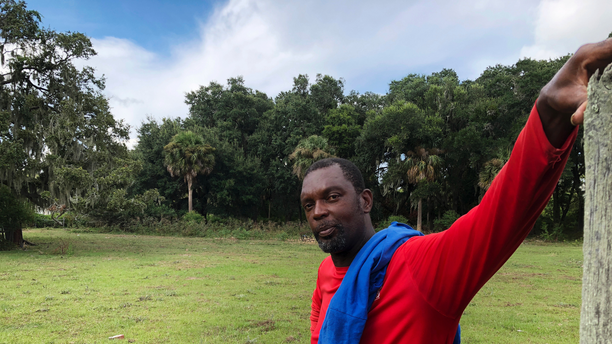 In this Sept. 11, 2018 photo, John Brown stands behind a fence for his cows outside his home on St. Helena Island, S.C. Brown and other residents of the island's Gullah community of slave descendants are watching Hurricane Florence as it approaches the Carolinas. St. Helena's Gullah residents have a long history of riding out storms, including a hurricane that killed an estimated 2,000 people in 1893. (AP Photo/Russ Bynum)