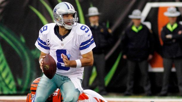 Dallas Cowboys quarterback Tony Romo (9) avoids a sack by Cincinnati Bengals defensive tackle Domata Peko (94) in the second half of an NFL football game, Sunday, Dec. 9, 2012, in Cincinnati. Dallas won 20-19. (AP Photo/Tom Uhlman)