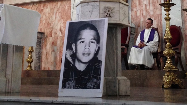 FILE - In this Oct. 14, 2014, file photo, a photo of Jose Antonio Elena Rodriguez, who was fatally shot by U.S. Border Patrol near the Mexico-U.S border, leans against a podium on a church altar during a memorial mass in Nogales, Sonora, Mexico. The civil rights case against Agent Lonnie Swartz over the Rodriguez' death will go forward after U.S. District Court Judge Raner C. Collins denied a part of his motion to dismiss the case. (AP Photo/Valeria Fernandez, File)