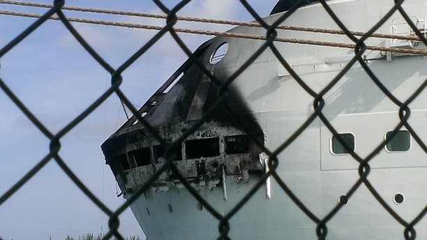 May 27, 2013: This photo provided by Royal Caribbean shows the fire-damaged exterior of Royal Caribbean's Grandeur of the Seas cruise ship, in Freeport, Bahamas. Royal Caribbean says the fire occurred on the mooring area of Deck 3 about 2:15 a.m., and was quickly extinguished, as the ship was en route to the Bahamas.