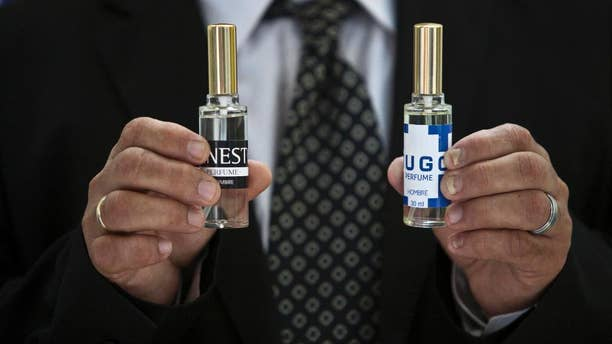 """A man shows two bottles of cologne, one called """"Ernesto,"""" honors guerrilla leader Ernesto """"Che"""" Guevara, and """"Hugo,"""" for the late Venezuelan president Hugo Chavez, in Havana, Cuba, Wednesday, Sept. 24, 2014. Formulated by a French company and produced in Cuba, the colognes are being presented this week at a Labiofam convention in Havana. (AP Photo/Franklin Reyes)"""